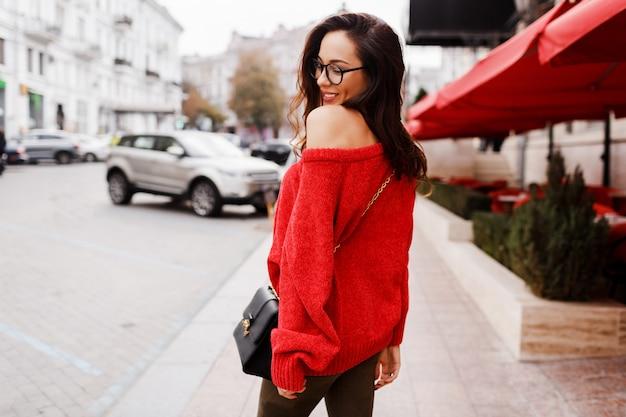 Blick von hinten. straßenmodebild der hübschen brünetten frau im trendigen roten pullover, frühlingsoutfit begehbar durch die straße.