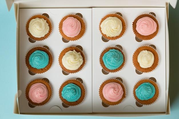 Blick von oben auf cupcakes mit streuseln und erdbeeren im karton