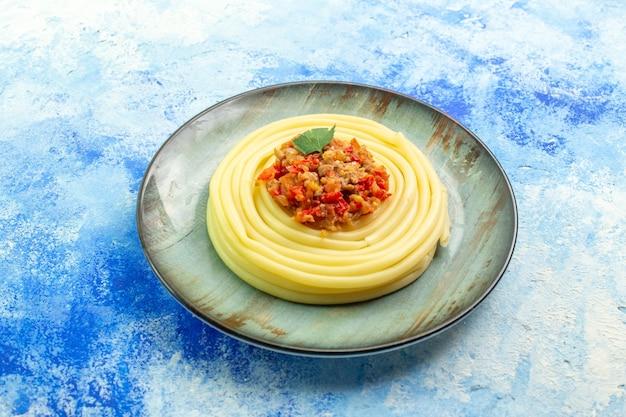Blick von oben auf das abendessen mit leckeren spagetti auf einem grauen teller auf blauem hintergrund