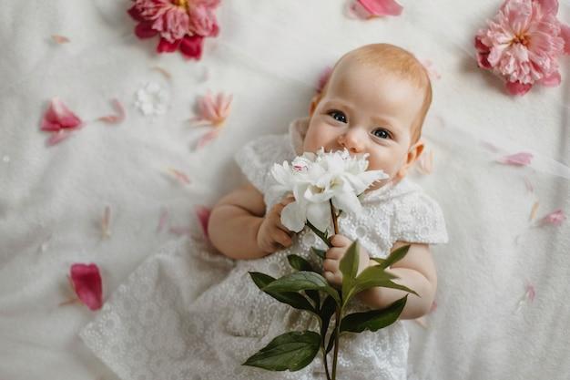 Blick von oben auf das baby, das in einem weißen süßen kleid gekleidet ist, das mit winzigen händen zarte weiße pfingstrosenblume hält, auf einer weißen decke liegt und mit blauen augen geradeaus schaut