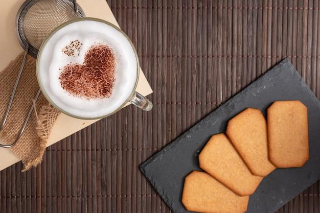 Blick von oben auf das frühstück mit keksen und kaffee mit herz