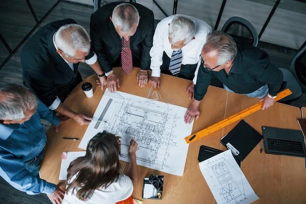 Blick von oben auf das gealterte team älterer geschäftsmannarchitekten, das sich im büro mit einer jungen frau trifft und mit plan arbeitet.