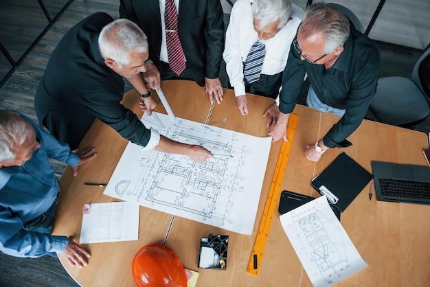 Blick von oben auf das gealterte team älterer geschäftsmannarchitekten, das sich im büro trifft und mit plan arbeitet.