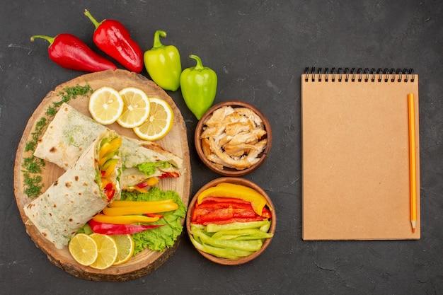 Blick von oben auf das in scheiben geschnittene shaurma leckere fleischsandwich mit zitronenscheiben auf schwarz