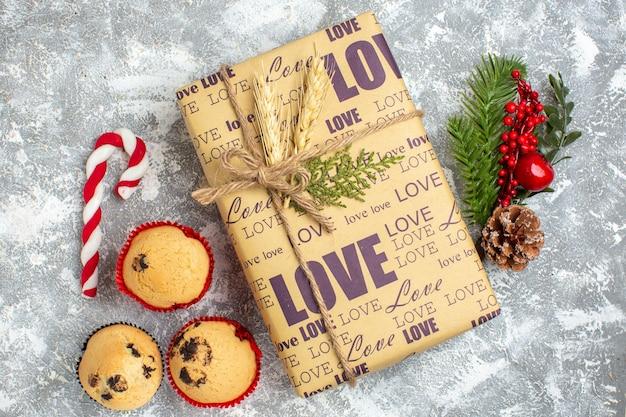 Blick von oben auf das schöne weihnachtsgeschenk mit liebesaufschrift kleine cupcakes süßigkeiten und tannenzweige dekoration zubehör nadelbaum kegel auf eisoberfläche