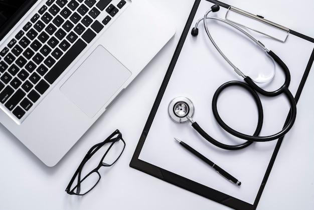 Blick von oben auf das stethoskop auf dem laptop in der zwischenablage und die brille auf dem weißen arztschreibtisch