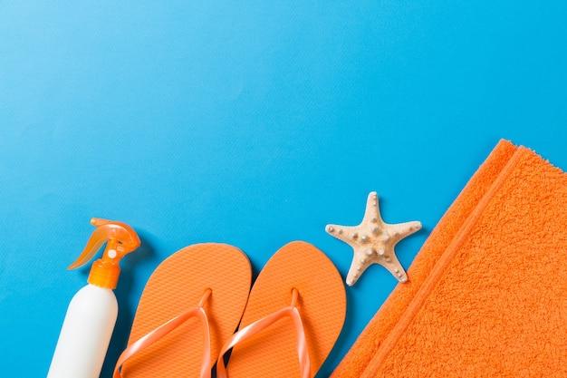 Blick von oben auf das strand-flachzubehör. sonnenschutzflasche mit muscheln, seestern, handtuch und flip-flop auf farbigem hintergrund mit kopierraum.