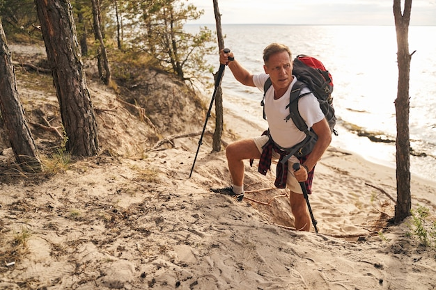 Blick von oben auf den athletischen reifen mann, der beim nordic walking den hügel über dem meer hinaufgeht
