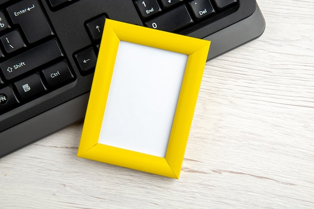 Blick von oben auf den gelben leeren bilderrahmen auf einem halben laptop auf weiß gestrippt