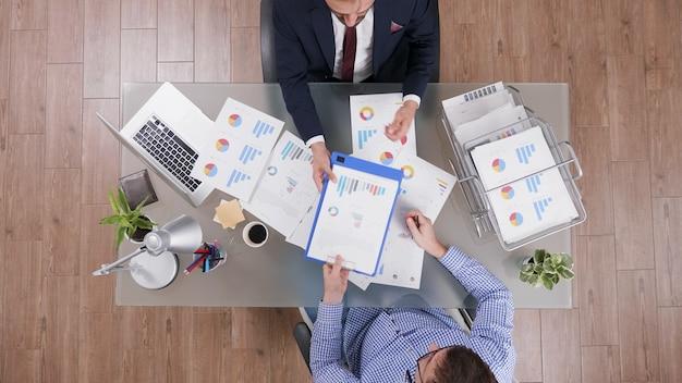 Blick von oben auf den geschäftsmann, der nach der analyse der unternehmensdokumente einen geschäftsvertrag unterzeichnet