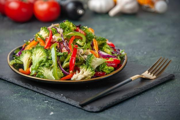 Blick von oben auf den holzhammer der weißen blume des frischen gemüses und den köstlichen veganen salat auf dunklem farbhintergrund