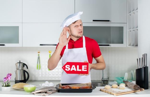 Blick von oben auf den jungen männlichen koch, der ein verkaufsschild zeigt und dem las-tratschen in der weißen küche zuhört?