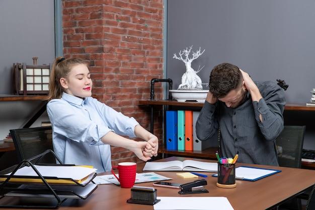 Blick von oben auf den jungen mann und seine kollegin, die am tisch sitzen und sich in der büroumgebung übermüdet fühlen