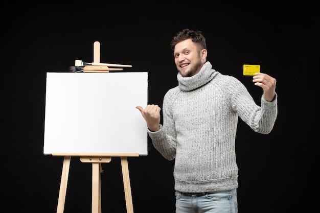 Blick von oben auf den jungen und lächelnden bärtigen künstler, der bankkarte auf isoliertem schwarz hält