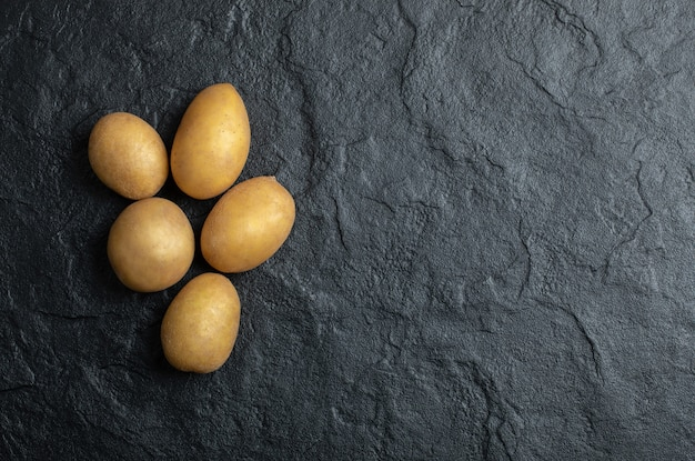 Blick von oben auf den kartoffelstapel. frische kartoffeln auf schwarzem steinhintergrund.