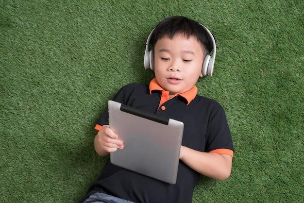 Blick von oben auf den kleinen jungen mit kopfhörern, der ein digitales tablet verwendet und lächelt, während er auf grünem gras liegt