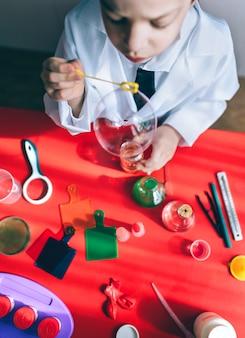 Blick von oben auf den kleinen wissenschaftler, der mit seifenblasen über dem roten tisch spielt?
