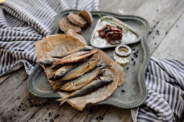 Blick von oben auf den leckeren rauchgetrockneten stöckerfisch auf dem papier auf dem metalltablett mit sonnengetrockneten tomaten, öl und brot auf der grau gestreiften serviette auf dem holztisch.