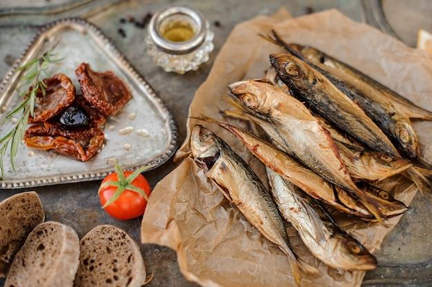 Blick von oben auf den leckeren rauchgetrockneten stöckerfisch auf dem papier mit sonnengetrockneten und frischen tomaten, öl und brot auf dem metallhintergrund.
