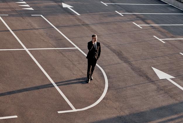 Blick von oben auf den mann in abendkleidung, der mit dem handy spricht, während er auf dem parkplatz mit pfeilzeichen steht ...