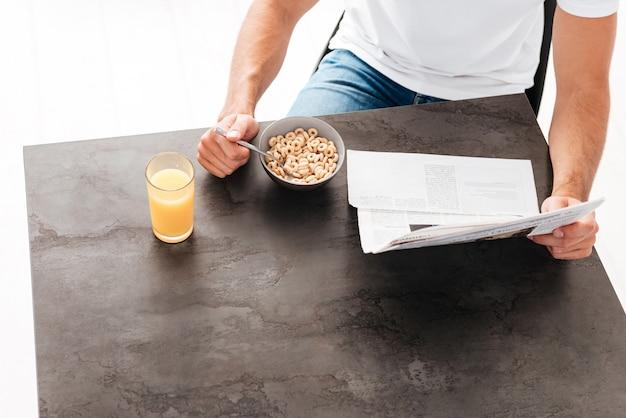 Blick von oben auf den mann mit zeitung, der müsli isst und saft zum frühstück am tisch trinkt