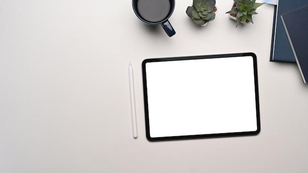 Blick von oben auf den modernen arbeitsplatz mit digitaler tablette mit leerem bildschirm und ausrüstung auf weißem tisch.