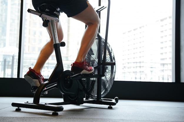 Blick von oben auf den muskulösen mann mit dem sich drehenden fahrrad