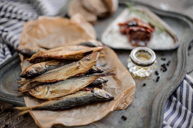 Blick von oben auf den rauchgetrockneten stöckerfisch auf dem papier auf dem metalltablett mit sonnengetrockneten tomaten, öl und brot auf der grau gestreiften serviette auf dem holztisch.