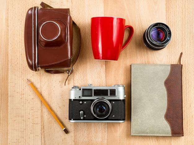 Blick von oben auf den retro-journalisten-arbeitsbereich mit kamera, objektiv, notizbuch, bleistift und tasse