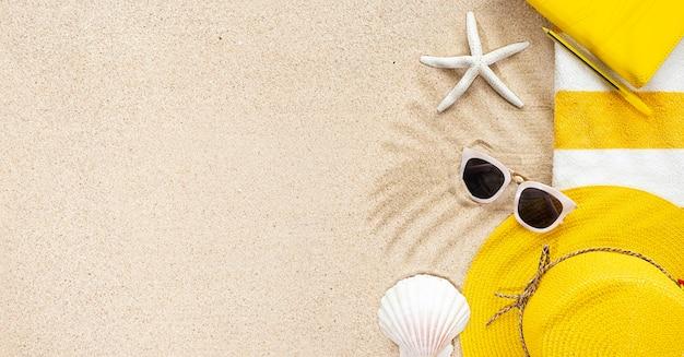 Blick von oben auf den sandstrand mit gestreiftem gelb-weißem handtuchrahmen, weißer sonnenbrille und muscheln. hintergrund mit kopienraum und sichtbarer sandbeschaffenheit. sommerkonzept