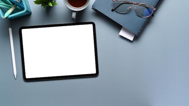 Blick von oben auf den stilvollen arbeitsbereich mit digitalem tablet, notebook, stylus-stift auf blauem tisch.