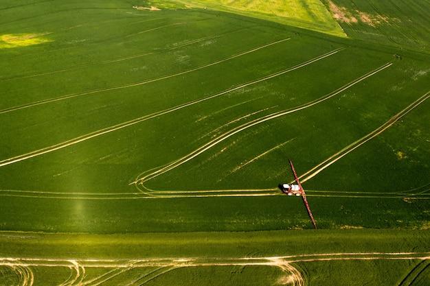 Blick von oben auf den traktor, der die chemikalien auf der großen grünen wiese versprüht