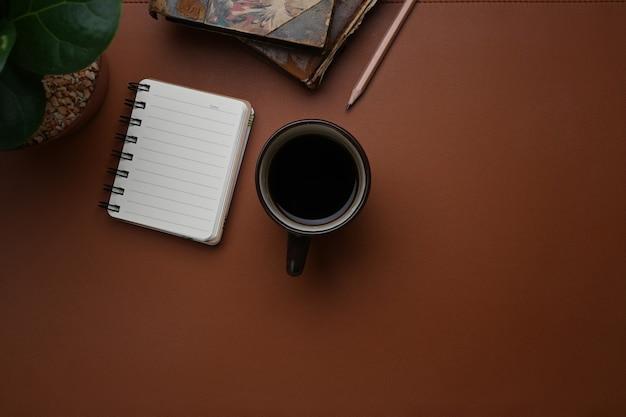 Blick von oben auf den vintage-arbeitsplatz mit kaffeetasse, notizbuch und kopienraum aus braunem leder.
