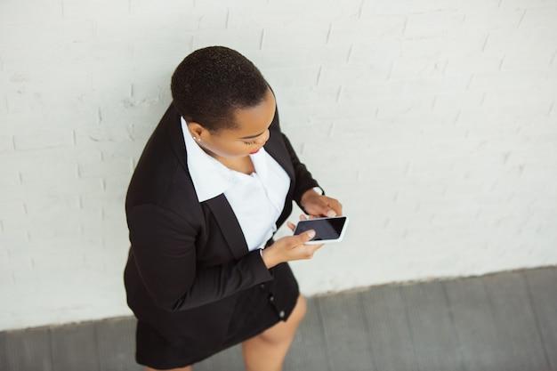 Blick von oben auf die afroamerikanische geschäftsfrau in bürokleidung, die telefon scrollt