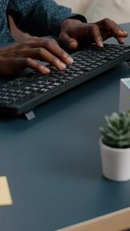 Blick von oben auf die afroamerikanischen hände des schwarzen mannes, die auf der computertastatur tippen