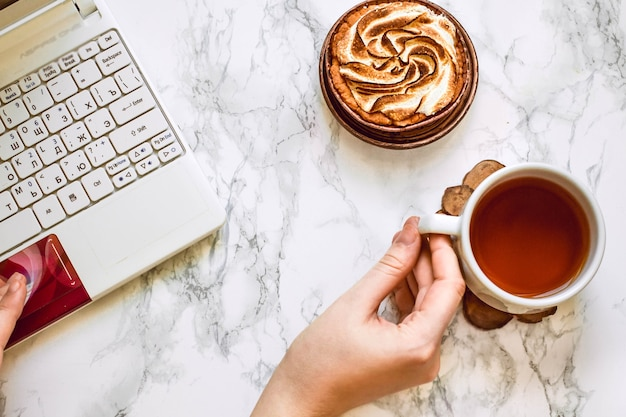 Blick von oben auf die hände der frau auf weißem marmor halten eine tasse tee und kuchen in der nähe eines weißen laptops.