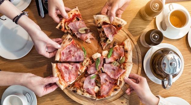 Blick von oben auf die hände der menschen, die scheiben pizza carbonara nehmen.