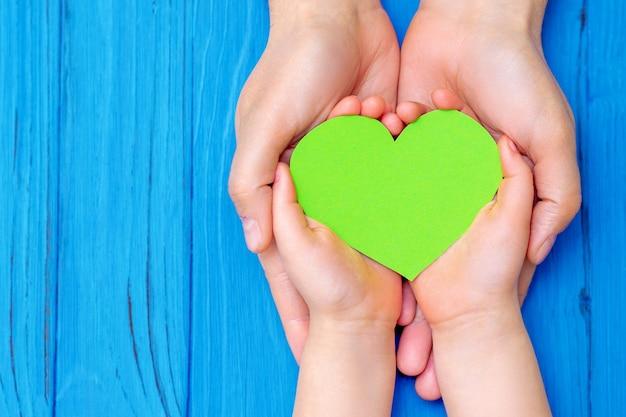 Blick von oben auf die hände des kindes und des vaters, die grünes papierherz auf blauem hintergrund aus holz halten