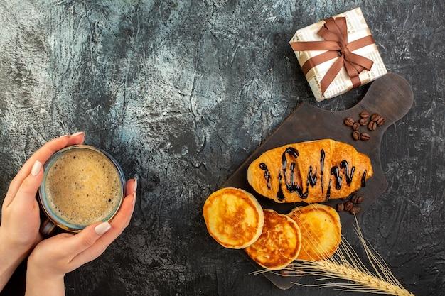 Blick von oben auf die hand, die eine tasse kaffee und ein leckeres frühstück mit pfannkuchen, croisasant und geschenkbox auf dunklem tisch hält
