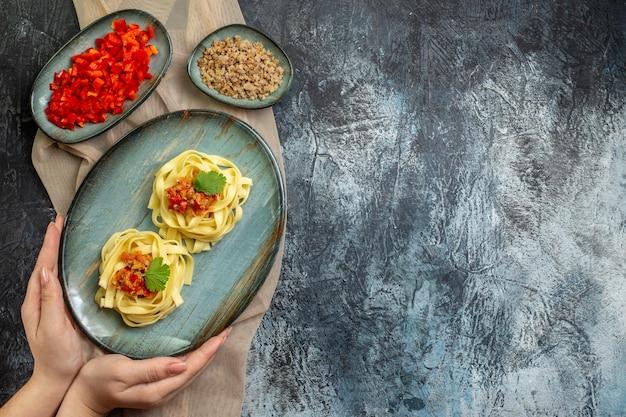 Blick von oben auf die hand, die einen blauen teller mit köstlicher pasta-mahlzeit mit tomaten und fleisch zum abendessen auf einem braunen handtuch hält