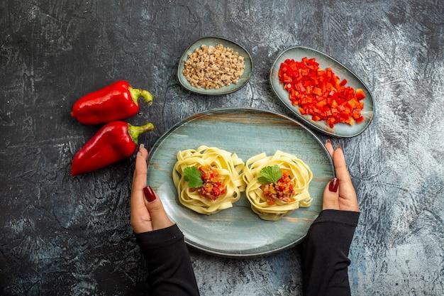 Blick von oben auf die hand, die gabel auf köstlichem pasta-essen auf einem blauen teller hält, und seine zutaten auf der eisoberfläche