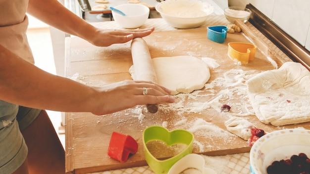 Blick von oben auf die junge frau, die teig herstellt und mit einem hölzernen nudelholz auf der küchentheke rollt