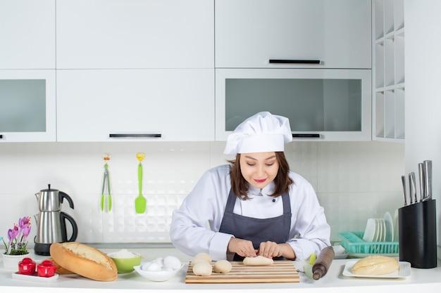 Blick von oben auf die junge glückliche köchin in uniform, die hinter dem tisch steht und gebäck in der weißen küche zubereitet