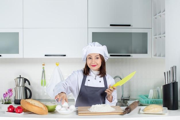 Blick von oben auf die junge konzentrierte köchin in uniform, die in der weißen küche speisen zubereitet