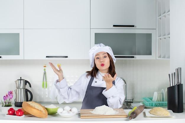 Blick von oben auf die köchin in uniform, die hinter dem tisch mit schneidebrett-brotgemüse steht und kussgeste in der weißen küche sendet