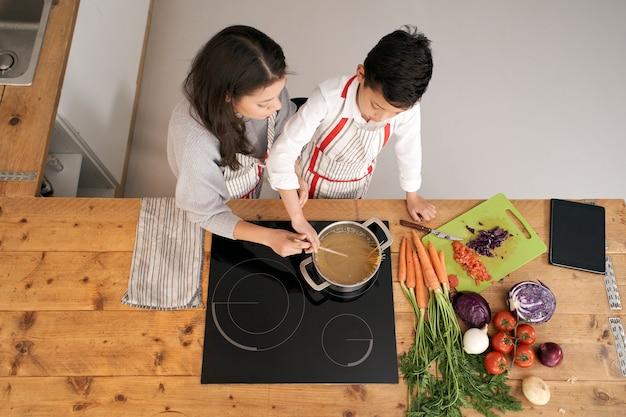 Blick von oben auf die küche eine alleinerziehende familie, die zusammen nudeln kocht mutter und sohn, die nudeln rühren
