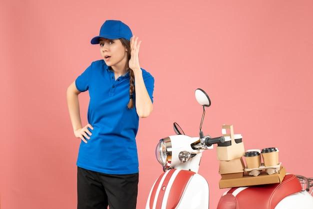 Blick von oben auf die kurierdame, die neben dem motorrad mit kaffee und kleinen kuchen steht und den letzten klatsch auf pastellfarbenem pfirsichhintergrund hört