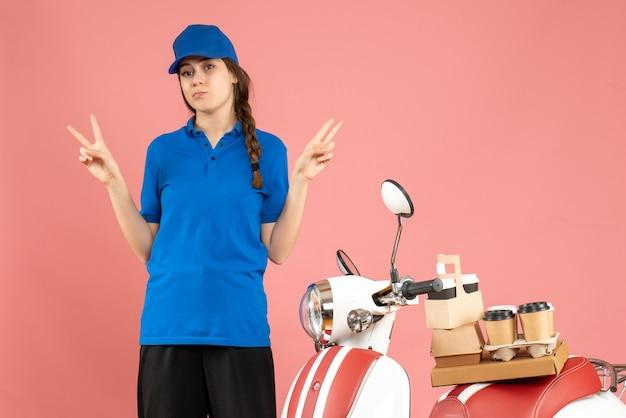 Blick von oben auf die kurierdame, die neben dem motorrad mit kaffee und kleinen kuchen steht und die siegesgeste auf pastellfarbenem pfirsichhintergrund macht