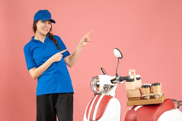 Blick von oben auf die lächelnde kurierdame, die neben dem motorrad mit kaffee und kleinen kuchen steht und auf pastellpfirsichfarbe zeigt