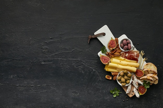 Blick von oben auf die leckere käseplatte mit obst, trauben, nüssen, oliven und geröstetem brot auf schwarzem schreibtisch.